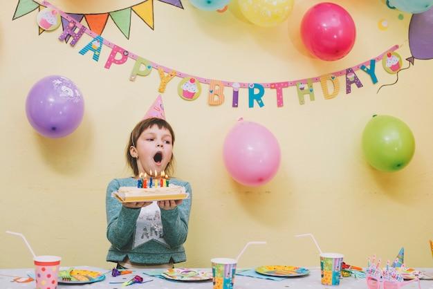 Dziewczyna dmucha świeczki na urodzinowym torcie