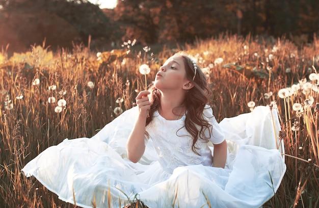 Dziewczyna dmuchająca nasionami z mniszka lekarskiego w jesienne popołudnie