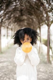 Dziewczyna Dmuchanie Balonu Na Zewnątrz Premium Zdjęcia