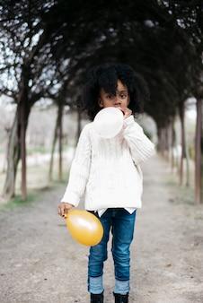 Dziewczyna dmuchanie balonu na zewnątrz