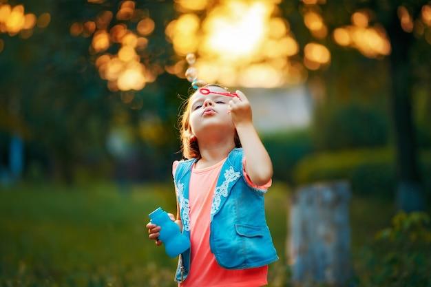 Dziewczyna dmuchanie baniek mydlanych na zewnątrz