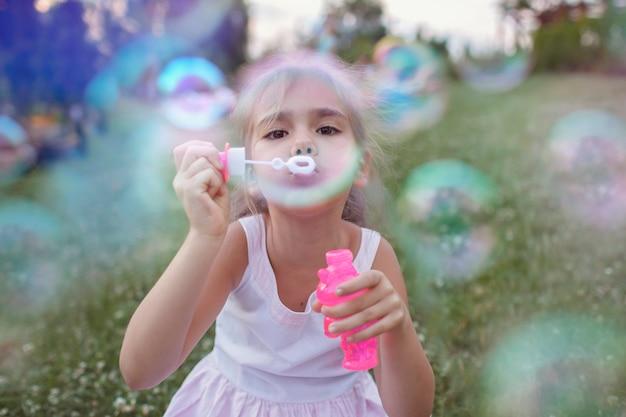 Dziewczyna dmuchanie baniek mydlanych w parku