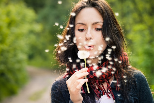 Dziewczyna dmuchanie na biały mniszek w lesie