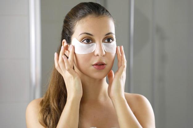 Dziewczyna do pielęgnacji skóry dotyka łatek z tkaniny maski pod oczami, aby zmniejszyć worki pod oczami