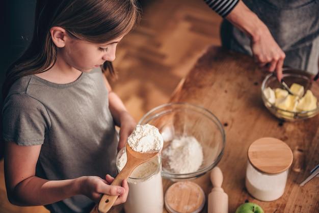 Dziewczyna, dodając mąkę do mieszania miski