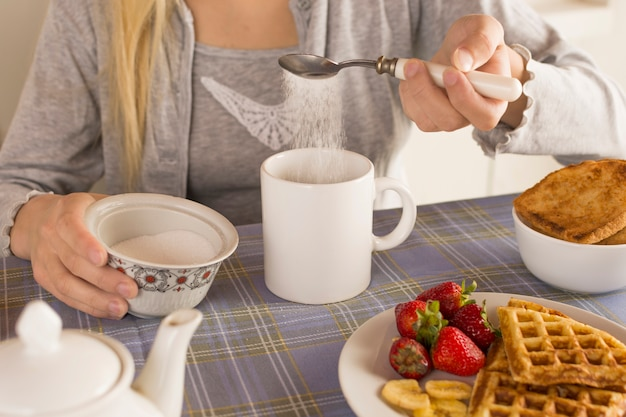 Dziewczyna dodaje cukier do herbaty