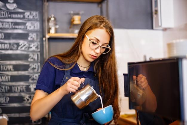 Dziewczyna dodaje mleko do kubka z kawą w kawiarni