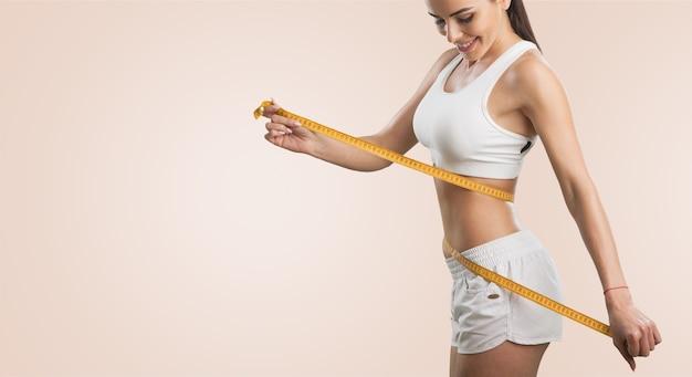 Dziewczyna dokonująca pomiarów jej ciała, białe tło.