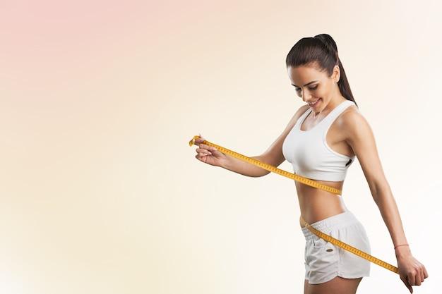 Dziewczyna dokonująca pomiarów swojego ciała,