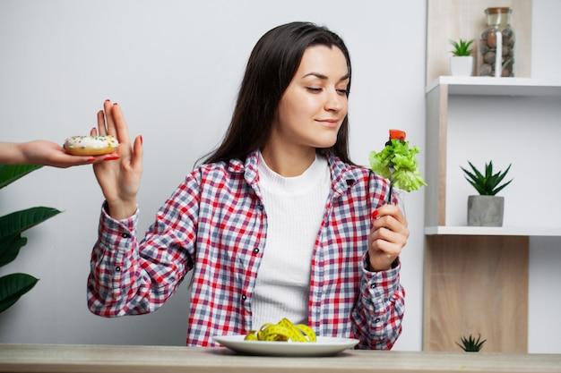 Dziewczyna dokonuje wyboru między zdrową a szkodliwą żywnością