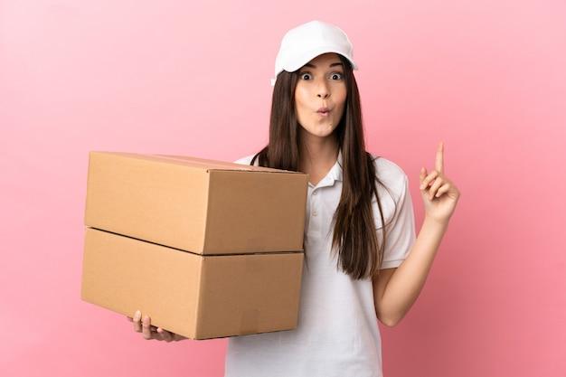 Dziewczyna dostarczająca nad odosobnioną różową ścianą, która zamierza zrealizować rozwiązanie, podnosząc palec w górę