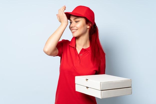 Dziewczyna dostarczająca pizzę, trzymająca pizzę nad izolowaną ścianą, zdała sobie sprawę z czegoś i planuje rozwiązanie