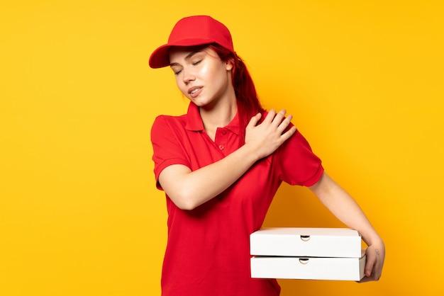 Dziewczyna dostarczająca pizzę trzymająca pizzę nad ścianą cierpiąca na ból ramienia za to, że podjęła trud