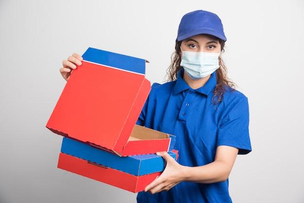 Dziewczyna dostarczająca pizzy otwierająca jedno z pudełek pizzy z maseczką medyczną na białym tle