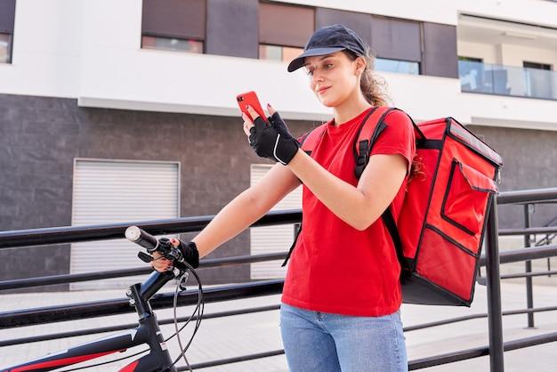 Dziewczyna dostarczająca rowerzystę za pomocą smartfona na ulicy