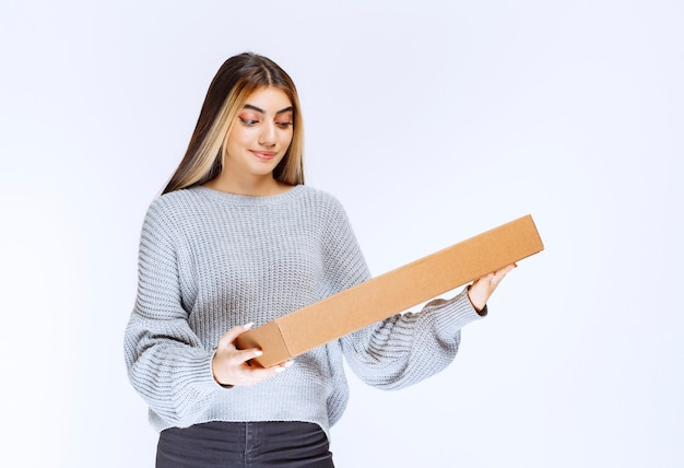 Dziewczyna dostarczyła klientowi kartonową paczkę.