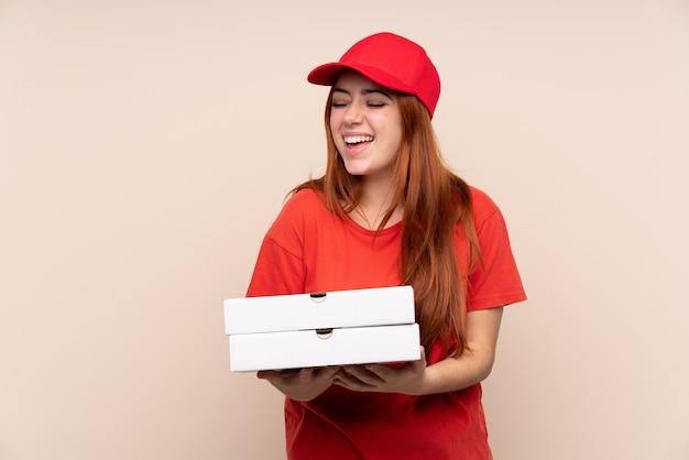 Dziewczyna dostawy pizzy nastolatka trzyma pizzę śmiejąc się