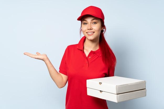 Dziewczyna dostawy pizzy trzyma pizzę nad izolowanym gospodarstwa wyimaginowanym na dłoni, aby wstawić reklamę