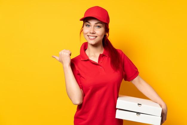 Dziewczyna dostawy pizzy, trzymając pizzę na białym tle, wskazując na bok, aby przedstawić produkt