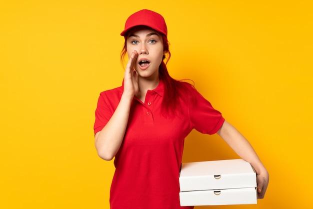 Dziewczyna dostawy pizzy trzymając pizzę na pojedyncze ściany z zaskoczenia i zszokowany wyraz twarzy