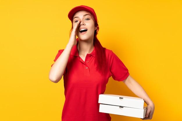 Dziewczyna dostawy pizzy, trzymając pizzę nad ścianą, krzycząc i ogłaszając coś