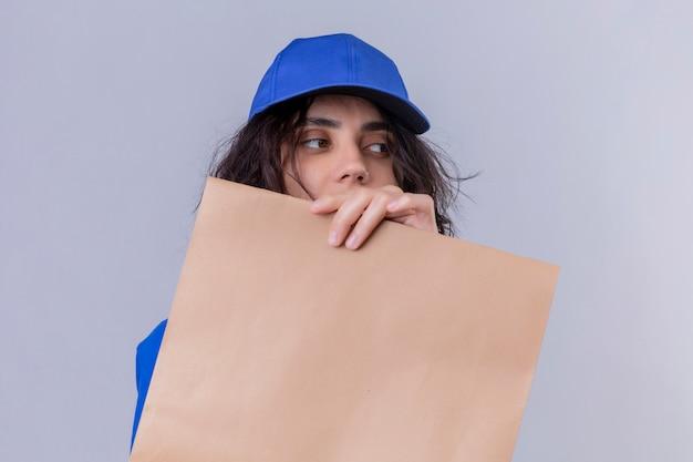 Dziewczyna dostawy w niebieskim mundurze i czapce, chowając się za pakietem papieru, patrząc na bok stojąc na białym