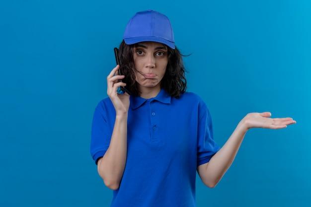Dziewczyna dostawy w niebieskim mundurze i czapce rozmawia przez telefon komórkowy nieświadoma i zdezorientowana z otwartymi ramionami, bez koncepcji stojącej na odosobnionym niebieskim