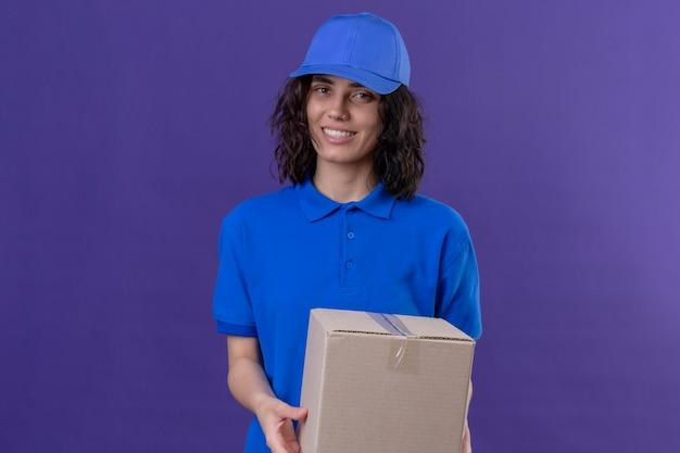 Dziewczyna dostawy w niebieskim mundurze i czapce trzyma pakiet pudełkowy uśmiechnięty przyjazny pozytywny i szczęśliwy pozycja