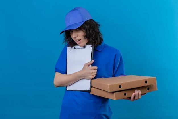 Dziewczyna dostawy w niebieskim mundurze i czapce trzyma pudełka po pizzy i schowek z prośbą o podpis patrząc onworked stojąc na odosobnionym niebieskim