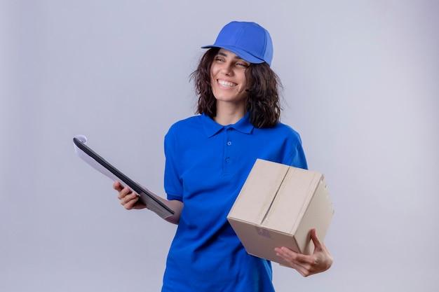 Dziewczyna dostawy w niebieskim mundurze i czapce, trzymając pakiet pole i schowek, uśmiechając się wesoło stojąc