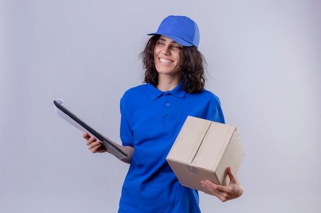 Dziewczyna dostawy w niebieskim mundurze i czapce, trzymając pakiet pole i schowek uśmiechnięty wesoło stojąc na białym