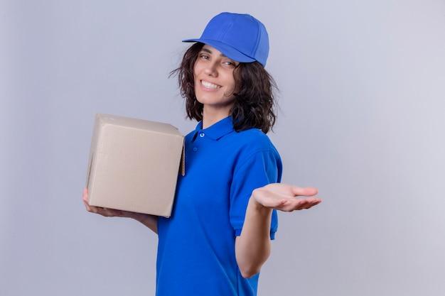 Dziewczyna dostawy w niebieskim mundurze i czapce, trzymając pudełko pakiet robi powitalny gest ręką uśmiechnięty przyjazny stojący na białym