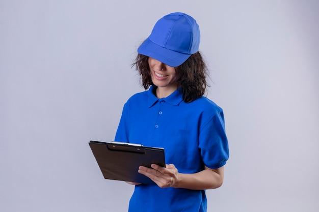 Dziewczyna dostawy w niebieskim mundurze i czapce trzymając schowek patrząc na to uśmiechnięty pewny siebie