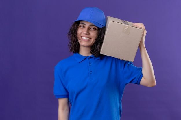 Dziewczyna dostawy w niebieskim mundurze i czapce trzymającej pudełko na ramieniu uśmiechnięta przyjazna pozycja pozytywna i szczęśliwa