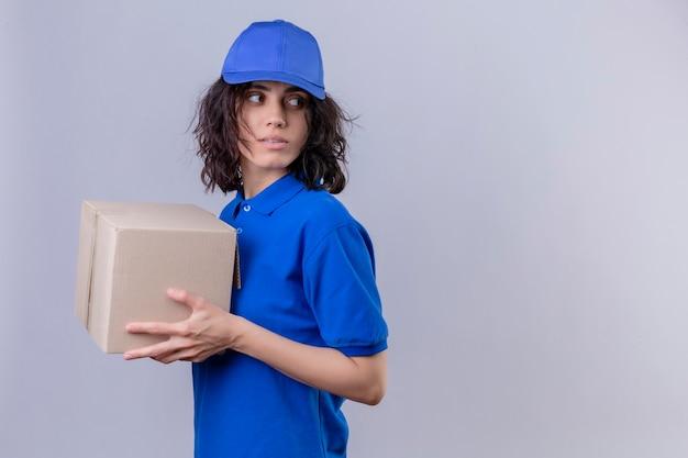 Dziewczyna dostawy w niebieskim mundurze i czapce trzymającej pudełko pakiet stojący bokiem, patrząc z poważną miną