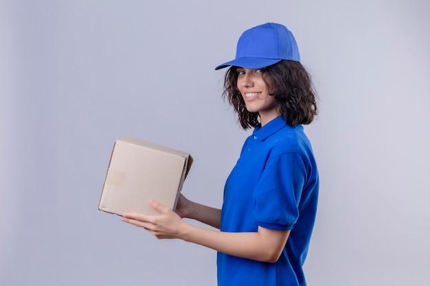 Dziewczyna dostawy w niebieskim mundurze i czapce trzymającej pudełko, stojąca bokiem, patrząc pewnie na odizolowaną białą przestrzeń
