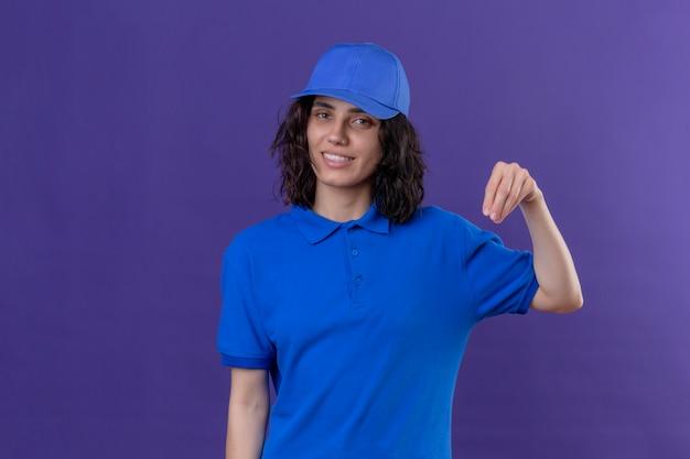 Dziewczyna dostawy w niebieskim mundurze i czapce wyglądająca pewnie, gestykulująca ręką, koncepcja języka ciała stojąca na odosobnionym fioletu