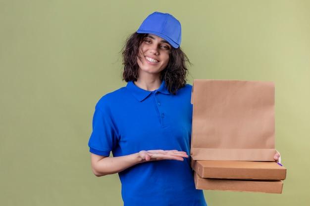 Dziewczyna dostawy w niebieskim mundurze, trzymając pudełka po pizzy i papierowy pakiet prezentując ramieniem dłoni uśmiechnięty radośnie uśmiechnięty na odizolowanej zieleni