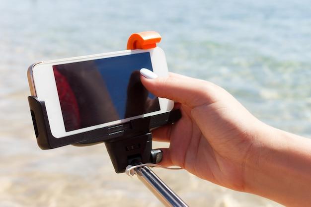 Dziewczyna dostosowuje aparat na kij selfie na morzu