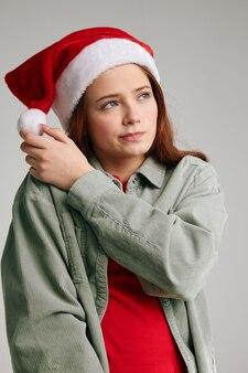 Dziewczyna dotyka pom-pom na świątecznej czapce boże narodzenie nowy rok szare tło