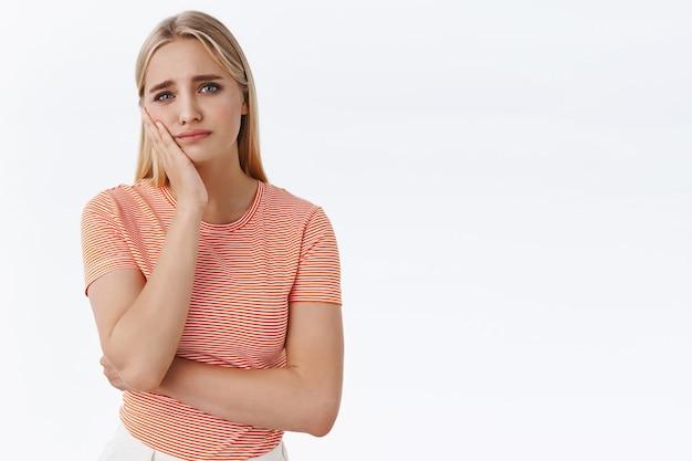 Dziewczyna dręczona bólem zęba, dotykaniem policzka i pochyloną głową, bruzdą brwi z powodu bolesnego uczucia, próchnica potrzebuje wizyty u dentysty, stoi niespokojnie dąsając się smutno, białe tło