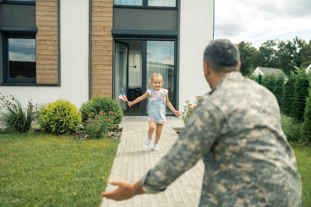 Dziewczyna działa. dziewczyna w letniej sukience czuje się niesamowicie wychodząc z domu i biegnąc do ojca