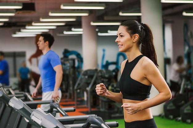 Dziewczyna działa na bieżni na siłowni