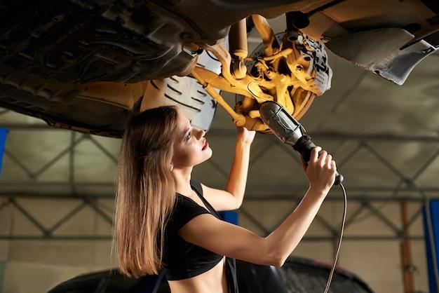 Dziewczyna egzamininuje podnoszącego samochód z lampą