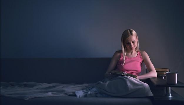 Dziewczyna entuzjastycznie czytająca książkę najlepiej sprzedający się dom pod dywanem na wygodnej sofie z lampką