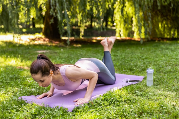 Dziewczyna fitness pompowania prasy na świeżym powietrzu w parku