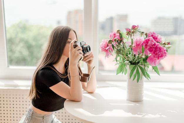 Dziewczyna fotograf robi fotografii piwonie