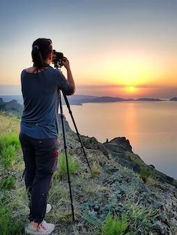 Dziewczyna fotograf robi zdjęcie wschodu słońca nad morzem czarnym na krymie latem