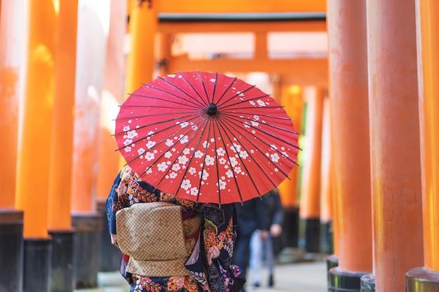 Dziewczyna gejszy ubrana w japońskie kimono wśród czerwonej drewnianej bramy tori