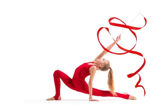 Dziewczyna gimnastyczka w czerwonym kombinezonie wykonuje ze wstążką na białym tle